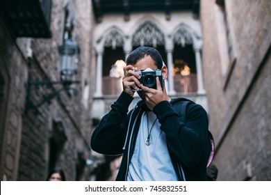 Cool young trendsetter, male tourist explores new culture or city in old european town. Makes photo on vintage analog camera, to prepare content for blog post on internet