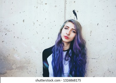 Cool young woman with blue hair and a septum piercing