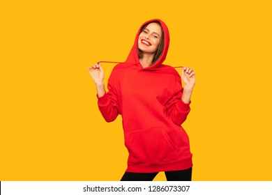 cool young woman posing with a red hoodie, hipster woman on yellow background