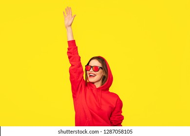 cool young woman in red hoodie saluting someone