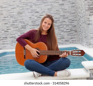 Cool young woman sitting on the edge of the pool playing guitar