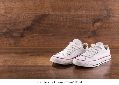 84d590eaf0c5 cool youth white gym shoes with red and blue stripes on brown parquet  wooden floor with