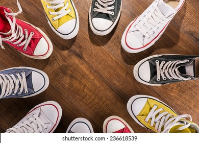 cool youth white yellow red blue black  gym shoes standing in circle  on brown parquet  wooden floor with copy place  top view