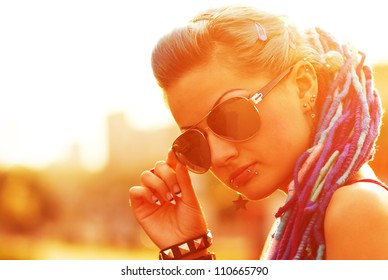 Coolest young chick posing at sunset.Punk teenage braided white girl posing in sunglasses.Portrait of punky cool teen girl.Fashionable female model with braids,lip piercing,nail work.Teenager fashion