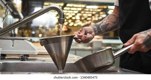 Cooling down. Close up photo of chef's hands with several tattoos holding cooked pasta in a colander under water over sink in the kitchen
