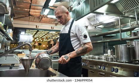 Cooling down. Serious professional chef holding cooked pasta in a colander under cold water in a restaurant kitchen
