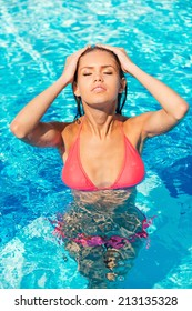 Cooling her body in pool. Top view of beautiful young woman in bikini adjusting her wet hair and keeping eyes closed while standing at the pool