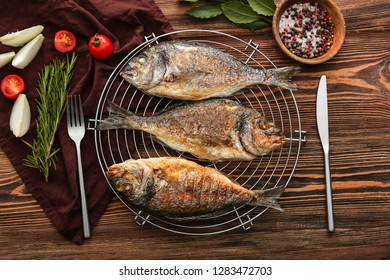 Cooling rack with grilled dorado fish, spices and vegetables on wooden background