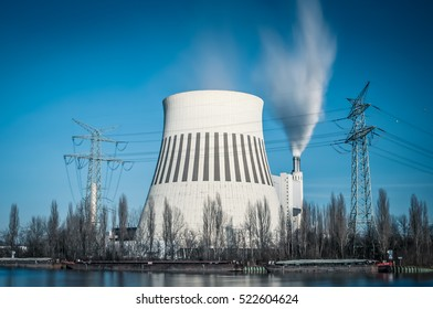 Cooling tower and smoke pipe of a heat and power plant against blue sky, long time exposure, desaturated filter style