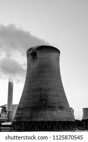 cooling tower with smoke plumes and large chimney in background