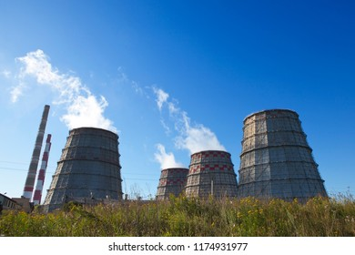 Cooling towers against a blue sky with wildflowers in the foreground