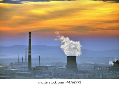 Cooling towers of a coal-fired power station with dramatic sky at sunrise.