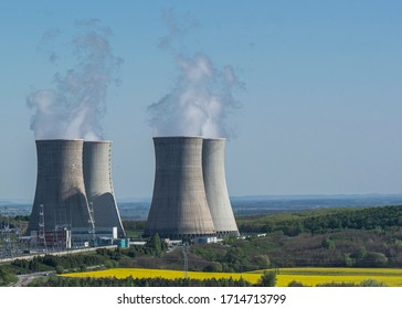 Cooling towers of nuclear power plant Mochovce with the yellow field of rapeseed in front of them.