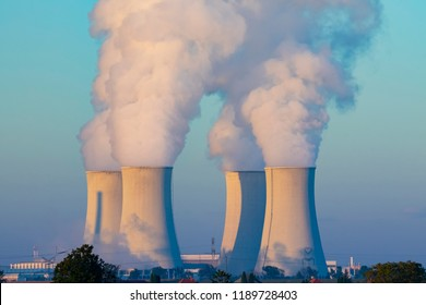 cooling towers with water steam in morning light, nuclear plant