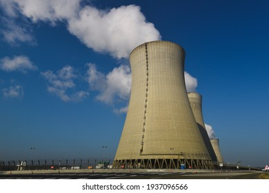 Cooling towers with water steam on a blue sky, nuclear plant