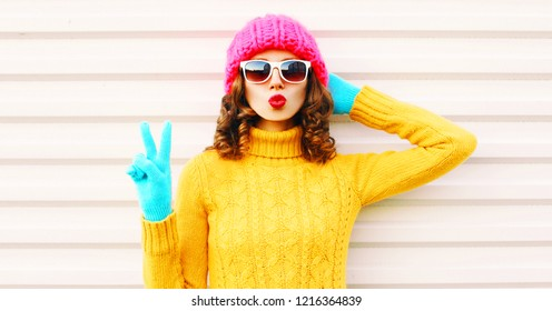 Cooll funny girl blowing red lips wearing colorful knitted yellow sweater pink hat in gloves over white background