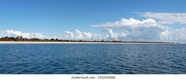 Coongul Beach, a tropical white pristine sandy beach panorama on the west coast of Fraser Island. A vibrant picturesque scenic panoramic seascape photo with a blue sky and white  cumulus cloud
