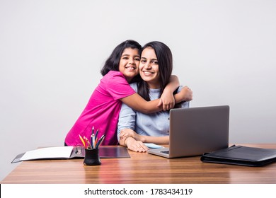 Cooperating Cute little Indian girl hugging Mother while she is busy working from home office with laptop at desk