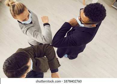 Cooperation, international teamwork, corporate unity concept. Multiethnic Business people partners teammates in medical protective face masks doing elbow bump in office at quarantine, top view