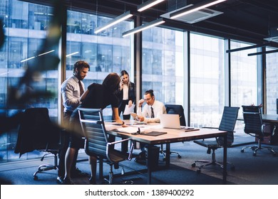 Cooperation process of professional male and female colleagues,business woman in formal suit communicate with operator via smartphone gadget while reading email from partners touch pad during teamwork - Shutterstock ID 1389400292