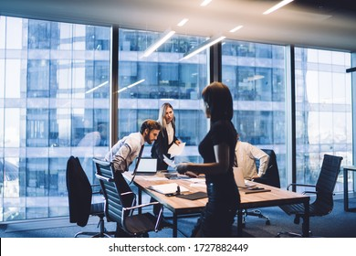 Cooperation process of professional male and female partners, intelligent corporate colleagues analyzing information from paper documents during working time in conference room with desktop