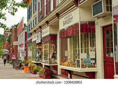 COOPERSTOWN, NY - SEPTEMBER 8, 2018: Shops, eateries, and baseball-themed attractions line the sidewalk on Main Street in this charming upstate New York town.