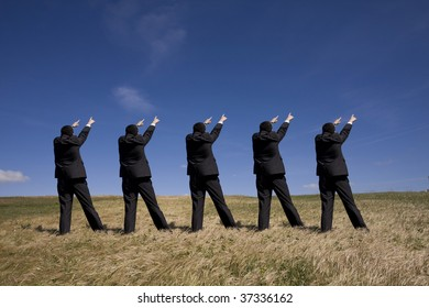 coordinated group of businessman pointing to the same side