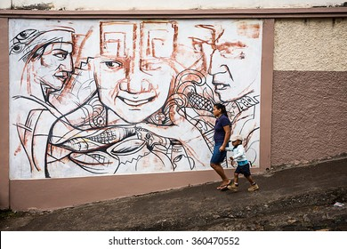 Copan, 11 march 2015, Honduras. A person walks in the street passing in front of a mural