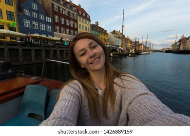 Copenaghen, Denmark, Europe - 1st May 2019 - European blonde girl smiling selfie during a boat trip between the canals of Nyhavn, Copenaghen, Danmark.