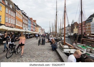 Copenhag, Denmark - July 13, 2016: People walking and cycling with colorful houses around them in Nyhavn,Copenhagen.