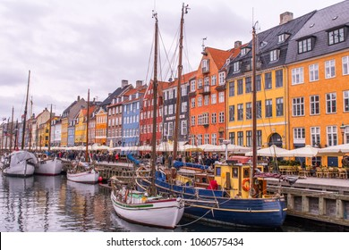 COPENHAGEN, APRIL 1, 2018:  Brightly painted restaurants prepare for lunch as tourists begin to walk around Nyhavn inlet containing sailboats