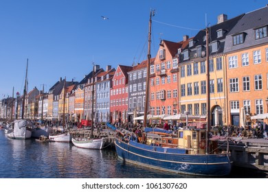 COPENHAGEN, APRIL 2, 2018:  Tourists slowly amble along Nyhavn in Denmark admiring the colourful buildings and ships