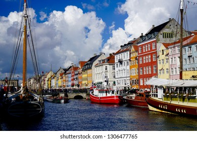 Copenhagen, Denmark - 09 09 2017: Famous colored houses and boats in Nyhavn with crowds and restaurants on the canal, white clouds in blue sky in day light