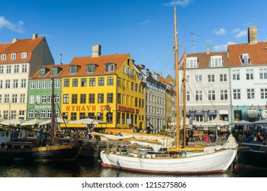 Copenhagen / Denmark - 10 24 2018: Tourists and citizens enjoying the famous colorful pier Nyhavn filled with colorful buildings and boats. Nyhavn is one of the major tourist attractions in Copenhagen