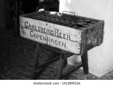 Copenhagen, Denmark - 18th November 2018: Old Vintage Carlsberg wooden crate to transport glass bottles of the alcoholic beer in the van to public houses and shops. Black white retro style background