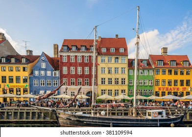 COPENHAGEN, DENMARK - 2014 Jun 09: View from the other side of canal to the many restaurants and seafront cafes on Nyhavn district (New Harbor), medieval port and bar street.