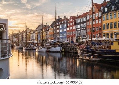 COPENHAGEN, DENMARK - 22ND MAY 2017: Buildings, architecture, boats and reflections along the Nyhavn at sunset. People can be seen.