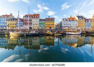 COPENHAGEN, DENMARK - 22ND MAY 2017: Buildings, architecture, boats and reflections along the Nyhavn during the day. Reflections and people can be seen.