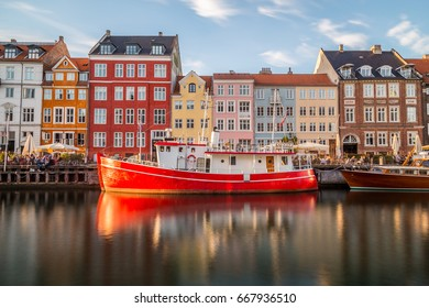COPENHAGEN, DENMARK - 22ND MAY 2017: Buildings along the Nyhavn in Copenhagen and a bright red boat. People can be seen.
