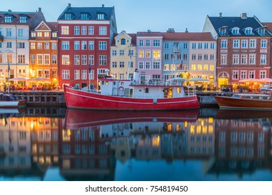 COPENHAGEN, DENMARK - 22ND MAY 2017: View of boats and buildings along the Nyhavn at night. People can be seen at restaurants and reflections can be seen in the water.