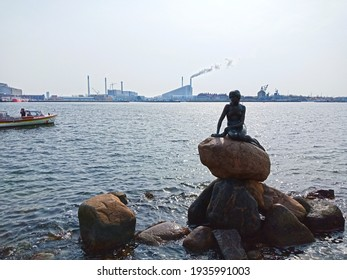 Copenhagen, Denmark - April 14, 2018- Silhouette of The Little Mermaid state with boat and factory background