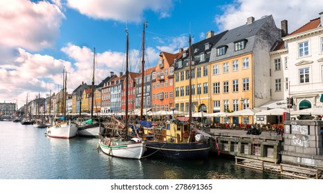 COPENHAGEN, DENMARK - APRIL 16 - Boats docked in the famous Hafenrundfahrt area, coloured buildings behind with unidentified people enjoying the bright sunshine, April 16, 2015 in Copenhagen, Denmark.