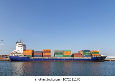 Copenhagen, Denmark - April 18, 2018: Side view of a container cargo ship anchored in the harbor