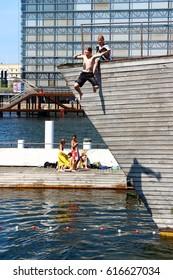 Copenhagen, Denmark - April 4, 2016: Children palying in Copenhagen docks, jumping into the outdoors river pool.