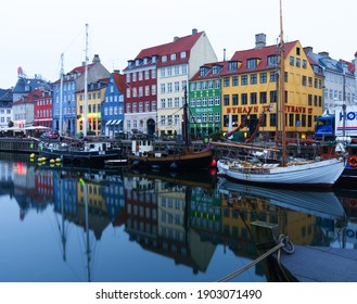 Copenhagen, Denmark - April 4 2017: Colorful houses and boats in canal at Nyhavn in early morning.