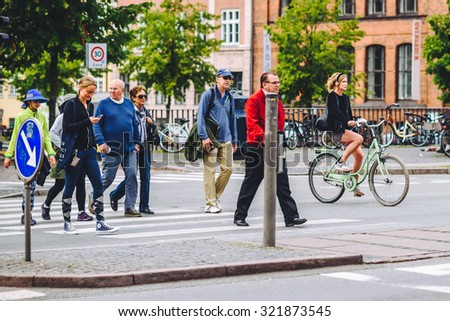 COPENHAGEN, DENMARK - AUGUST 01, 2015: People going by bike in the city. A lot of commuters, students and tourists prefer using bike instead of car or bus to move around the city.
