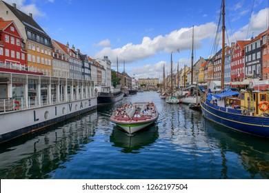 COPENHAGEN, DENMARK - AUGUST 10 2018: Tourboat cruises on Nyhavn district in Nyhavn, Copenhagen.