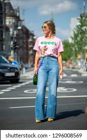 COPENHAGEN, DENMARK - AUGUST 11 2018: Street style during Copenhagen fashion week Spring Summer 2019. Outfit: beautiful Gucci pink bambi print T-shirt, jeans and green Cult Gaia bag.