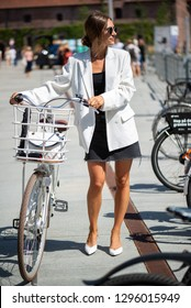COPENHAGEN, DENMARK - AUGUST 11 2018: Siw Melchiorsen from ELLE Denmark on a city bicycle wearing black and white with white CHANEL bag during CPH fashion week SS2019
