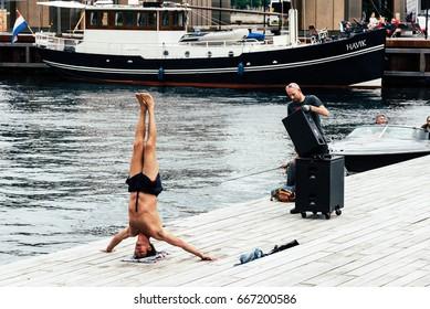 Copenhagen, Denmark - August 12, 2016: Man practicing yoga outdoors in the pier of the harbor of Copenhagen